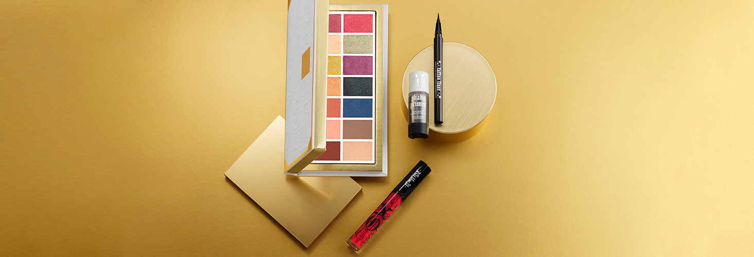 Edge of Reality Eyeshadow Palette, Tattoo Liquid Eyeliner, Shake Eyeshadow primer, and XO Lip Vinyl Lipgloss on a yellow background